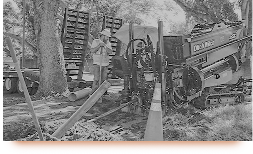 A black and white image of a worker managing a Ditch Witch drill.